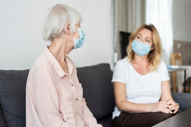 Woman visiting her relative at nursing home and wearing medical mask