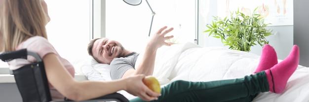 아픈 환자 개념을 방문하는 침대에서 환자 근처 휠체어에 앉아 여자 방문자