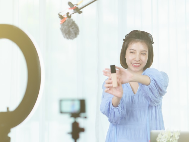 Woman vlogger holding skin care products in hands,  while recording video for blog.