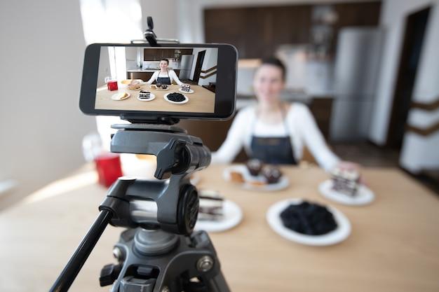 Женщина-влогер записывает видео для канала еды. повар шеф записывает видео для видеоблога с телефона