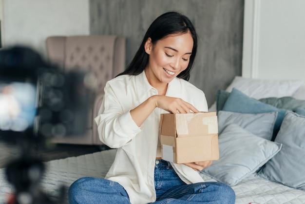 Женщина ведет видеоблог и смотрит в коробку
