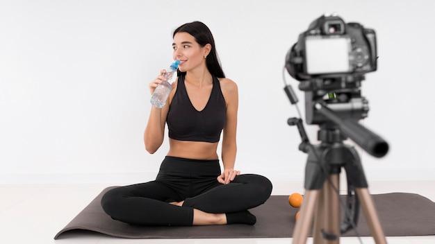 Женщина ведет видеоблог дома во время тренировки и пьет воду