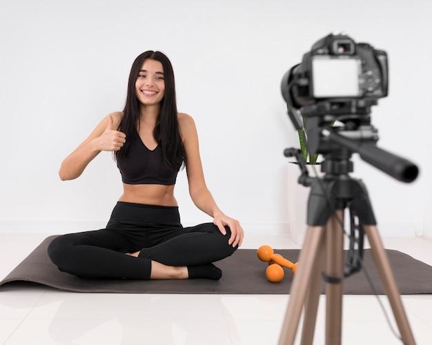 Женщина ведет видеоблог дома во время тренировки и показывает палец вверх