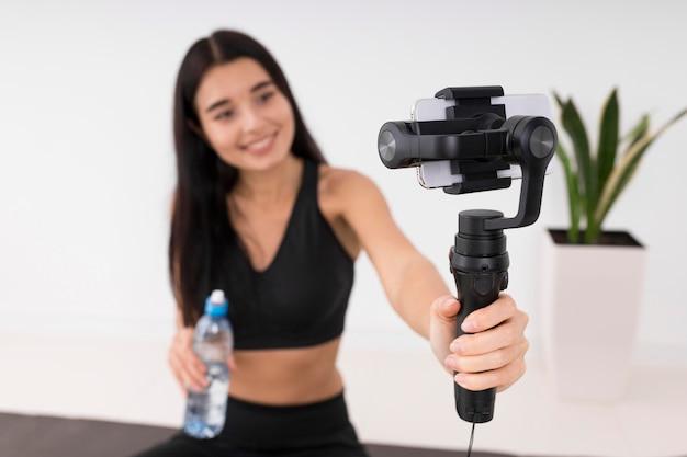 Женщина ведет видеоблог дома во время тренировки и держит бутылку воды
