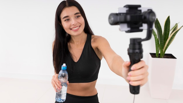 Женщина ведет видеоблог дома во время тренировки со смартфоном