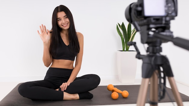 Женщина ведет видеоблог дома с камерой во время тренировки