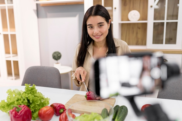 Woman vlogging at home with vegetables