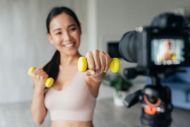 Женщина ведет видеоблог в спортивной одежде дома