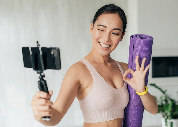 Woman vlogging while holding her fitness mat