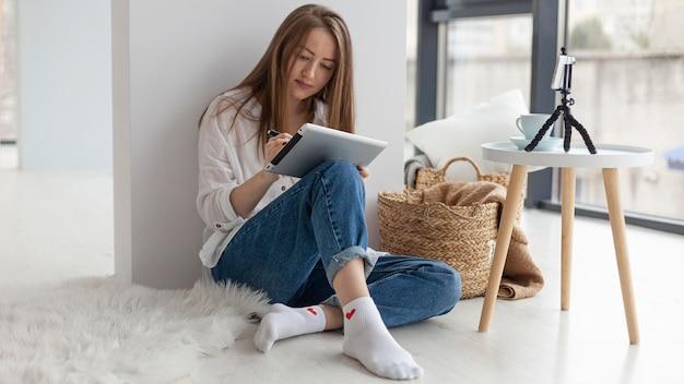 Женщина ведет видеоблог со своим телефоном в помещении во время работы на планшете