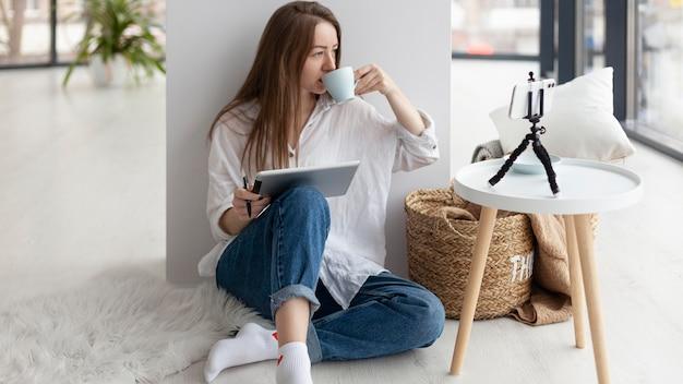 Женщина ведет видеоблог со своим телефоном в помещении