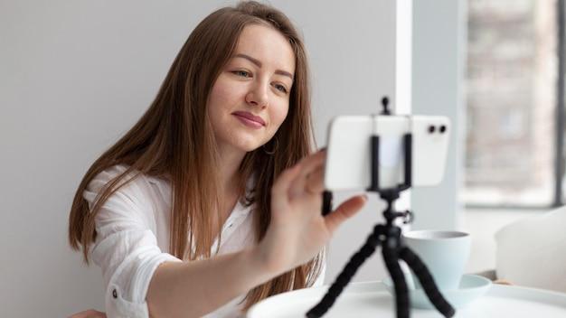 Женщина ведет видеоблог со своим телефоном
