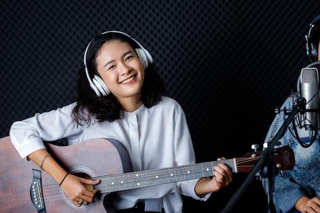 歌を録音するギターとヘッドフォンを身に着けている女性ボーカリスト