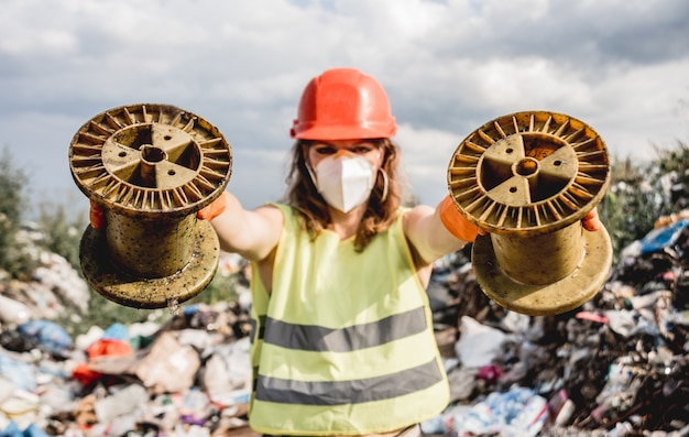 Woman volunteer helps clean the field of nuclear waste and plastic garbage. earth day and ecology.