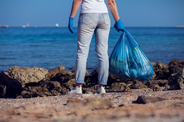 Женщина-волонтер в белой футболке с большим синим мешком собирает мусор на пляже. концепция загрязнения окружающей среды