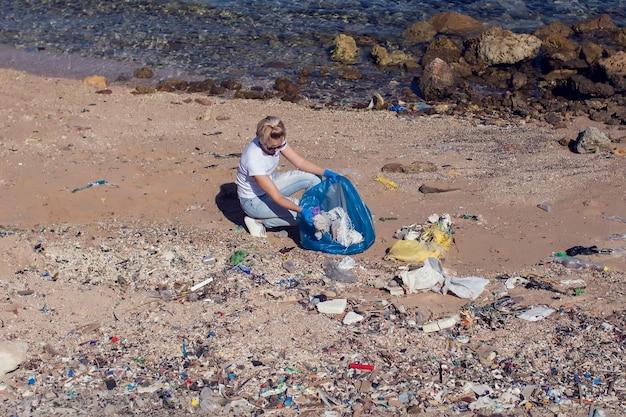 Женщина-волонтер с большим синим мешком, собирающая мусор на пляже. концепция загрязнения окружающей среды