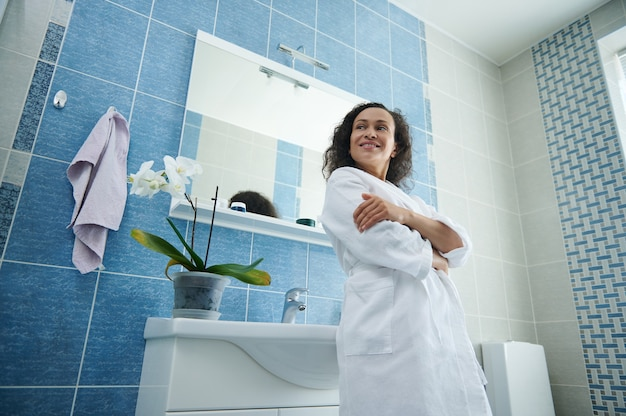 Woman in waffle bathrobe posing with crossed arms in front of the camera leaning on the sink in her home bathroom. morning hygiene