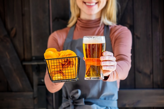 Woman waiter holds beer and chips