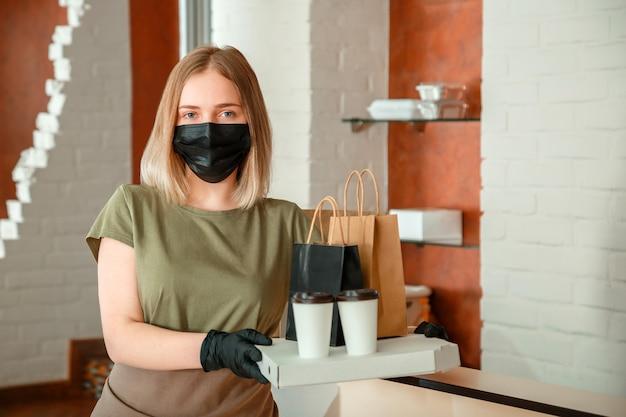 保護用の医療用マスクと手袋をはめた女性のウェイターが、テイクアウトの注文に対応します。都市のcovid 19ロックダウン、コロナウイルスのシャットダウン中にテイクアウトの食事を与えるウェイター。フード ピザ コーヒーの配達。