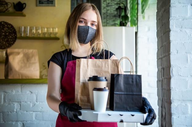 보호용 의료 마스크와 장갑을 낀 여성 웨이터는 테이크아웃 주문과 함께 일합니다. 도시 covid 19 잠금, 코로나바이러스 폐쇄 동안 웨이터가 테이크아웃 식사를 제공합니다. 음식 피자 커피 배달.