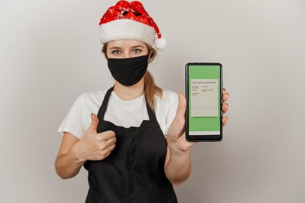 サンタの帽子と保護マスクの女性ウェイターは、covidワクチン接種証明書とスマートフォンを保持します