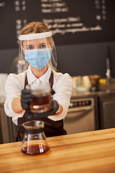 커피 바에서 일하는 제복을 입은 여성 웨이터