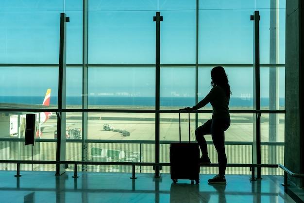 Woman waiting for airplane at airport terminal using smartphone - fuerteventura - spain