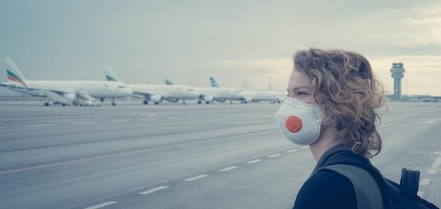 Женщина ждет регистрации в фойе аэропорта. использует маску рта и носа для защиты от вирусов. отменено авиасообщение из-за эпидемии коронавируса