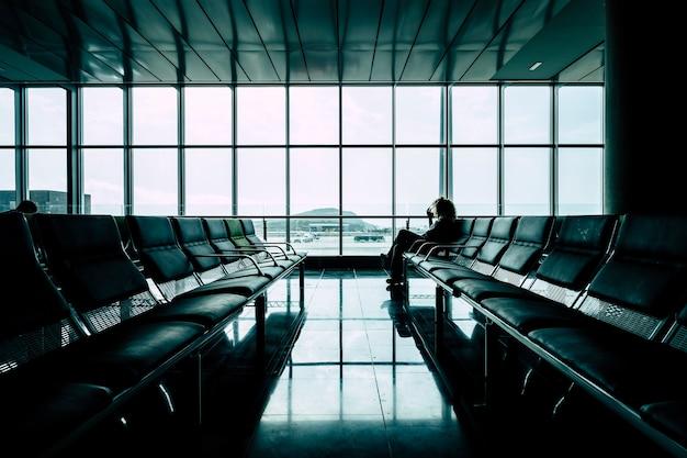 ゲートエリアの空港で彼女の飛行を待っている女性-到着または出発の概念で飛行機を遅らせる