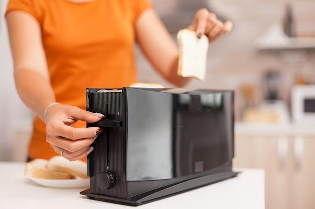 전기 토스터에서 볶은 빵이 터지기를 기다리는 여자.