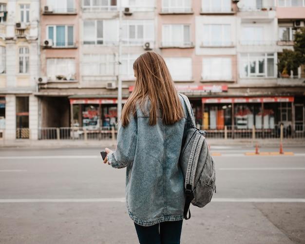 총 뒤에서 버스를 기다리는 여자
