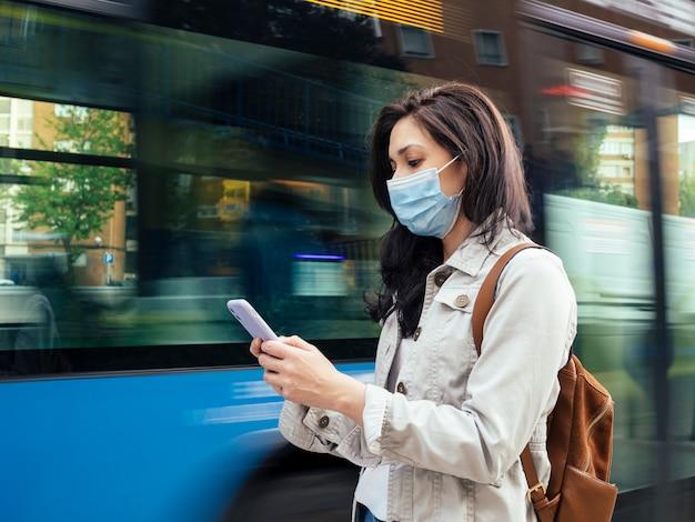 Женщина ждет автобуса. она носит защитную маску.