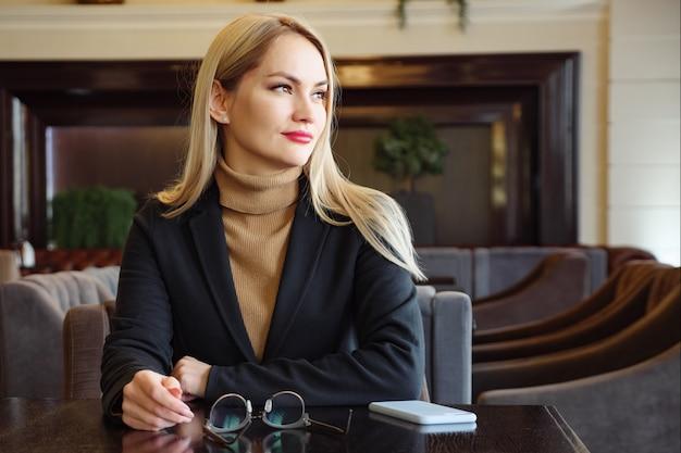Женщина ждет меню и смотрит в камеру. очки, телефон на столе.