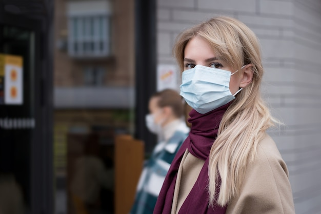 Woman waiting in line on the street outside the door during coronavirus pandemic