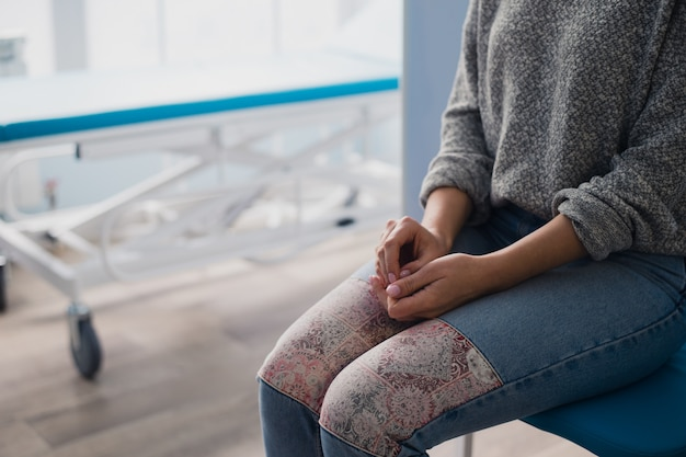 Woman waiting for medical examination sitting on treatment couch