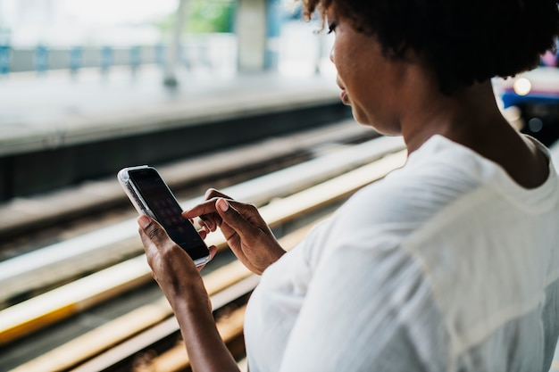 Woman waiting and playing on her phone