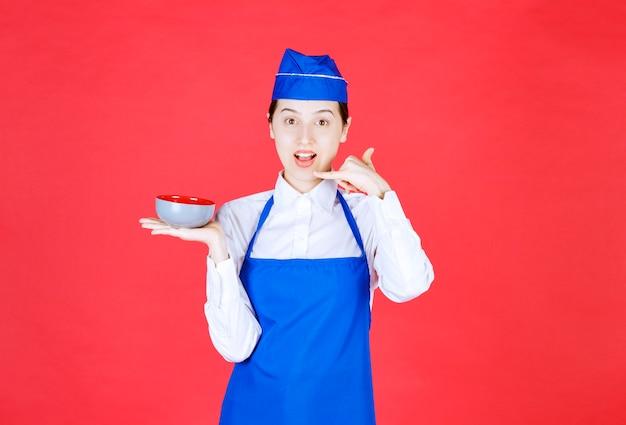 Женщина-официантка в униформе держит миску и делает жест телефонного звонка на красной стене.
