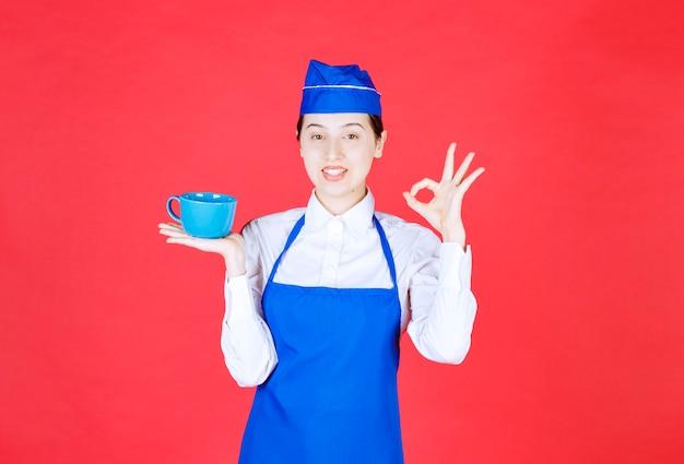 제복을 입은 여자 웨이트리스가 그릇을 들고 빨간 벽에 확인 제스처를 보여줍니다.