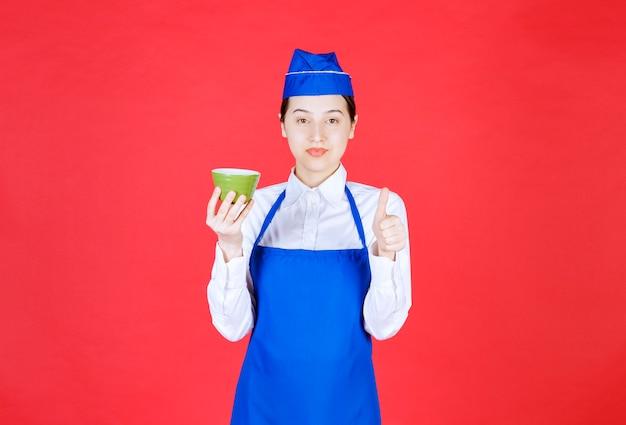 녹색 그릇을 들고 엄지손가락을 보여주는 제복을 입은 여자 웨이트리스.