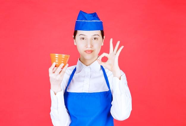 주황색 그릇을 들고 확인 사인을 하는 제복을 입은 여자 웨이트리스.