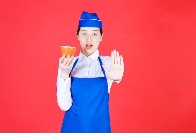 제복을 입은 여성 웨이트리스가 주황색 그릇을 들고 정지 제스처를 취합니다.