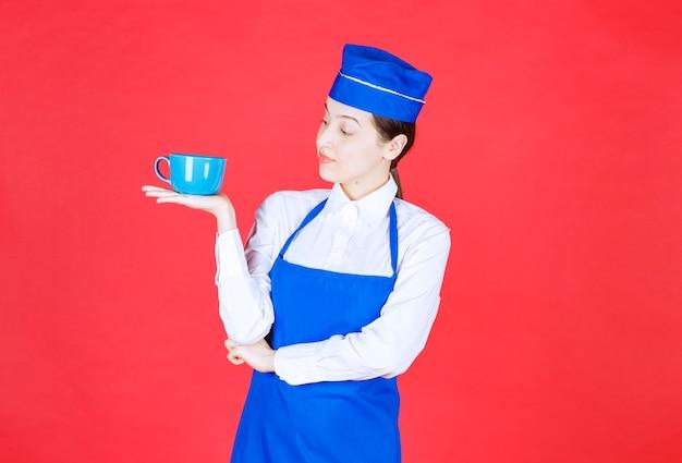 빨간 벽에 그릇을 들고 제복을 입은 여자 웨이트리스.
