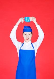 제복을 입은 여자 웨이트리스가 붉은 벽에 머리 위로 그릇을 들고 있습니다.