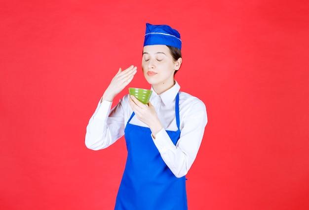 제복을 입은 여자 웨이트리스가 녹색 그릇을 들고 서 있습니다.