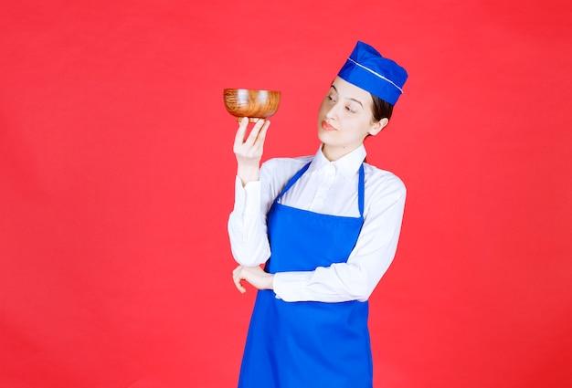 제복을 입은 여자 웨이트리스가 나무 그릇을 들고 서 있습니다.