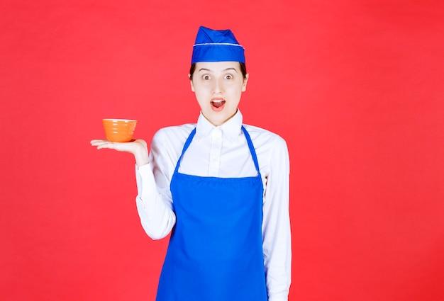 주황색 그릇을 들고 제복을 입은 여자 웨이트리스.