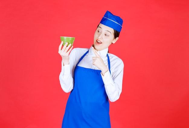 유니폼을 입고 녹색 그릇을 가리키는 여자 웨이트리스.