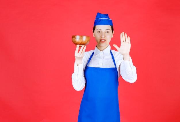 제복을 입은 여성 웨이트리스가 나무 그릇을 들고 정지 신호를 만들고 있습니다.