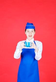 Cameriera donna in uniforme in piedi e in possesso di una ciotola sul muro rosso.