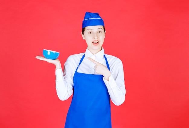 Cameriera donna in uniforme in piedi e indicando una ciotola sul muro rosso. Foto Gratuite